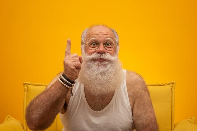 Улыбается старший с длинной белой бородой человек, делая один раз подписать жест рукой