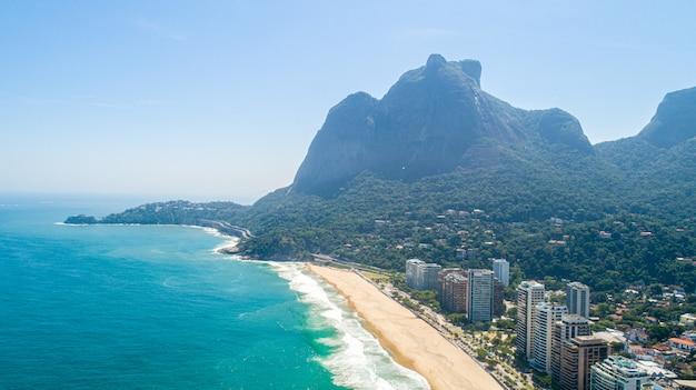 熱帯のビーチからの眺め。熱帯の黄色い砂のビーチで波が壊れます。美しい熱帯のビーチの空中