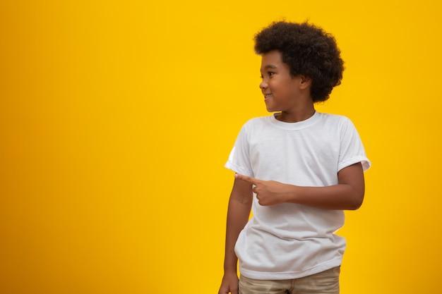 Мальчик афроамериканца с черными волосами силы на желтом цвете. улыбающийся черный парень с черными волосами власти. черный мальчик с черной силой волос. африканского происхождения.
