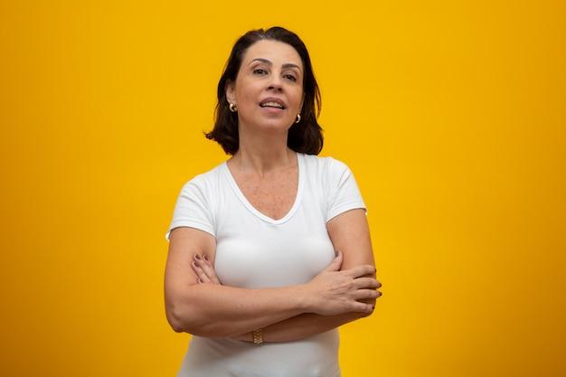 黄色の腕を組んで魅力的な中年の女性