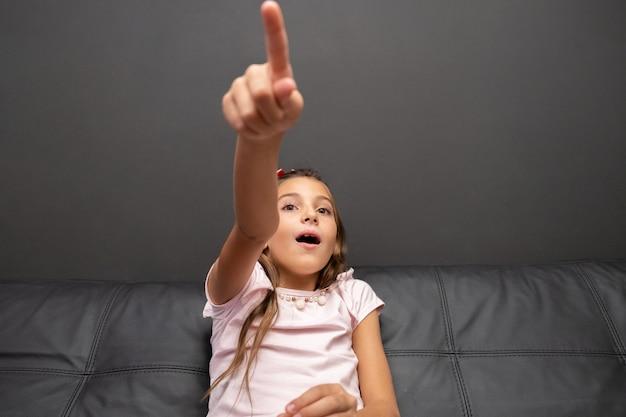 自宅のリビングルームのソファに座って夜にテレビを見て幸せな少女