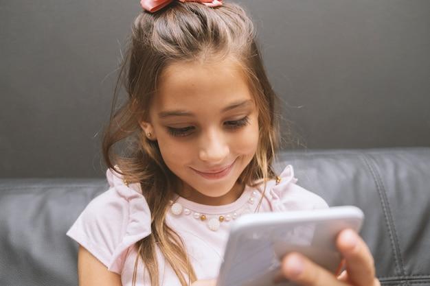 Красивая маленькая девочка играет в игру или смотреть видео на смартфоне мобильного телефона