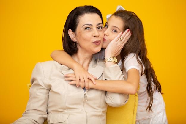 Маленькая девочка целует маму