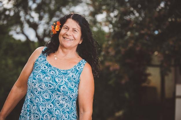 彼女の髪に花と自然の中で笑顔の美しい女性の肖像画