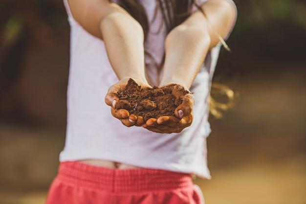 Ребенок рука держит почву, подготовить к посадке дерева