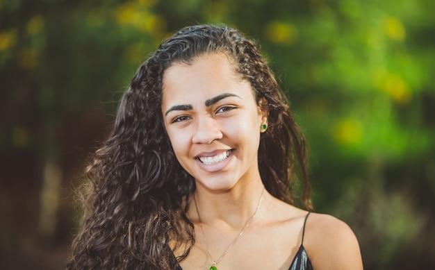 Портрет улыбающегося красивой молодой женщины в природе