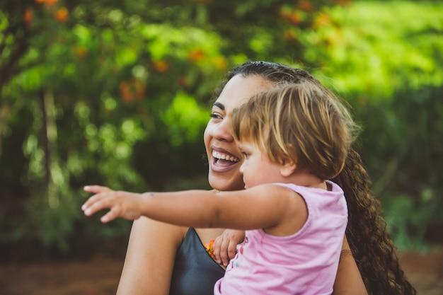 Радостная молодая женщина и маленький милый ребенок девочка, указывая в парке