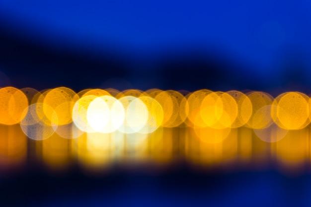 ぼやけた黄色ライトとダークブルースクリーンの背景
