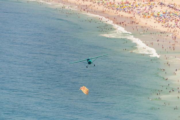 リオデジャネイロのコパカバーナビーチの上を飛ぶ小型飛行機。