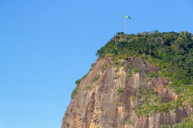 Камень руля с флагом бразилии на вершине, вид с пляжа у руля в рио-де-жанейро