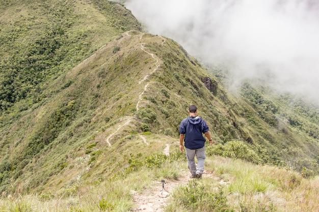 マンティケイラ山脈のミナスジェライス州の山脈(山頂)の頂上を歩く男。