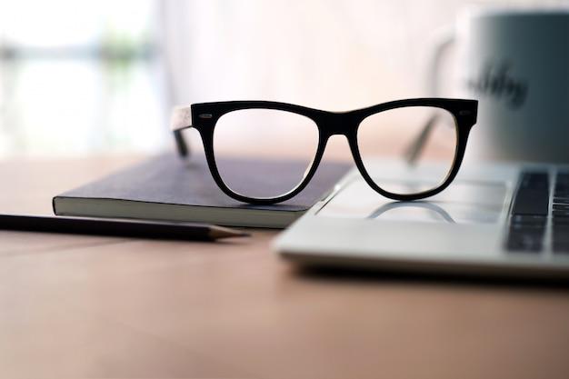 ホワイトコーヒーのマグカップ、ノート、鉛筆、メガネを机の上の作家のキャリア
