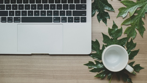 木製のテーブルと一杯のコーヒーにラップトップ