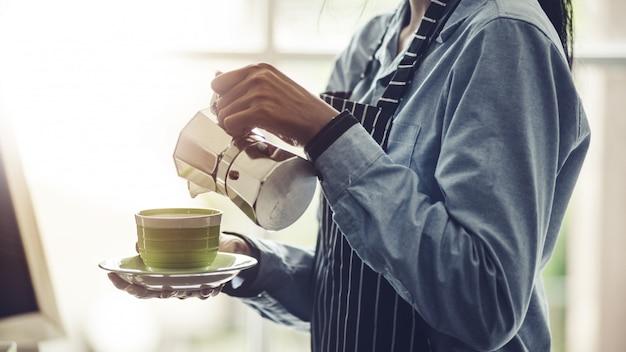 Бариста готовит эспрессо, американо, капучино, латте, мокко и готовит кофейный напиток.