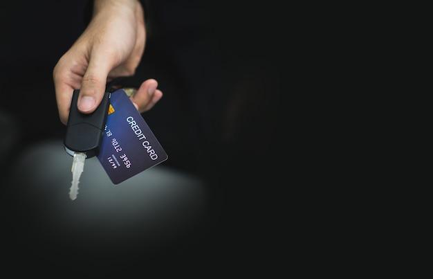 若い男は彼の手に車のキーを持つクレジットカードで支払うことによって車の借金を支払いました。