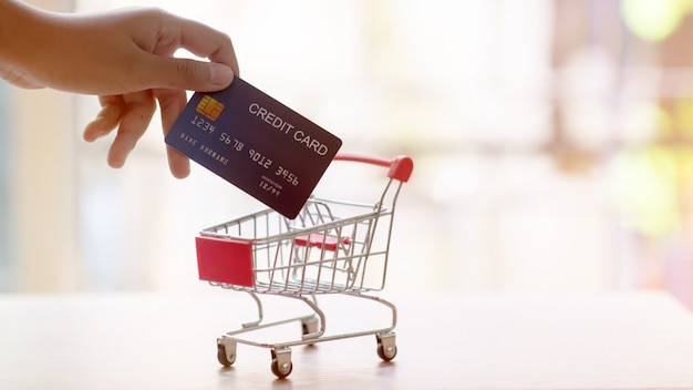 クレジットカードでショッピングカート。オンラインショッピングと配信サービスのコンセプト。クレジットカードで支払う。