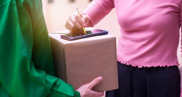 Женщина-домохозяйка подписывает посылку отправителя на смартфоне в эпоху цифровых технологий, отвечая на мир технологий без границ.