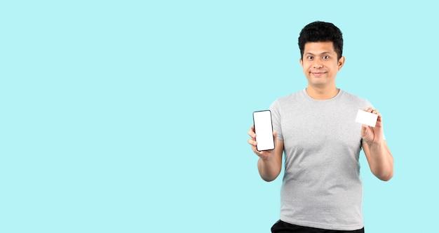 アジア人男性の幸せな使用スマートフォン保留預金カードが分離された有料購入サービス