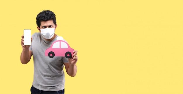 Азиатский человек, носящий маску, держит смартфон и руку держит красный бумажный автомобиль на желтой стене
