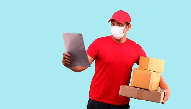 Маска азиатского человека нося для того чтобы защитить от зародыша и вируса. держа с посылкой в картонных коробках и держа документ на светло-голубой стене