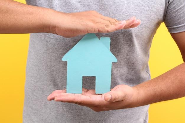 アジアの男の手が黄色の壁に青い紙の家の形を保持します。