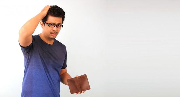 Шокирован, удивлен потерял дар речи мужчина держит пустой кошелек на белом.