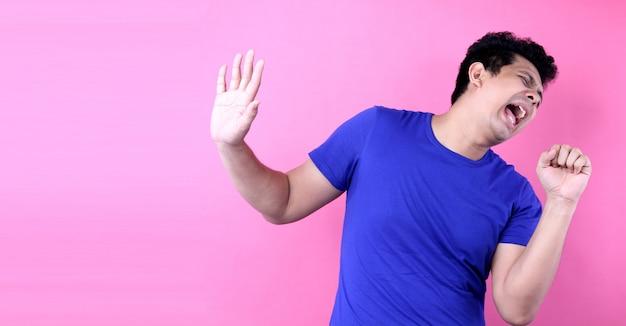スタジオでピンクの背景に立っている間大声で歌っている肖像画ハンサムなアジア男
