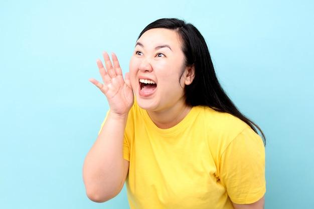 アジアの女性の肖像画は叫んで、スタジオで青い背景に分離された彼の口に手します。