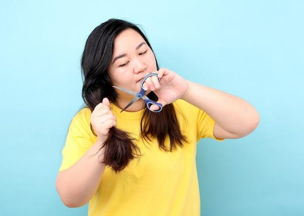 アジアの女性の肖像画は、スタジオで青色の背景に彼女の傷んだ髪をカットしたいです。