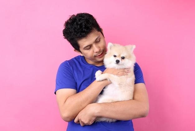 Портрет азиатских мужчин держит поморскую собаку с любовью и играет с ним на розовой стене.