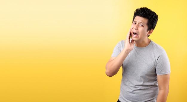 歯痛のコンセプト。痛みを感じて、頬を手で抱えて、黄色い壁に悪い歯の痛みに苦しんでいる若いアジア人男性の屋内ショット。