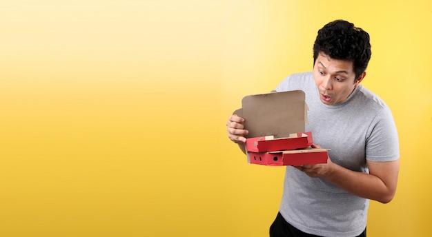Молодой азиатский мужчина держит коробку с итальянской пиццей, напуганный с удивлением,