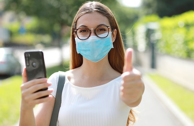 都市通りに親指を現してスマートフォンを保持している医療マスクを持つ若い美しいビジネス女性