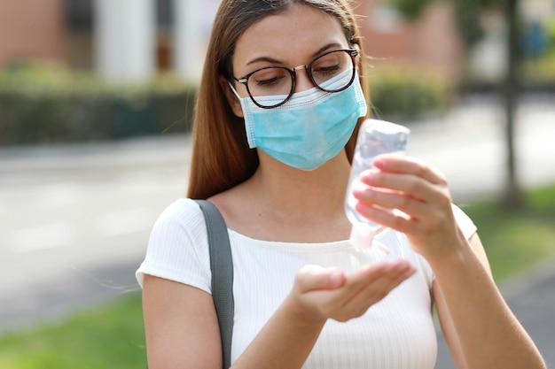 都市通りで手消毒ゲルを使用してサージカルマスクを持つ若い女性の肖像画。防腐剤、衛生およびヘルスケアの概念。