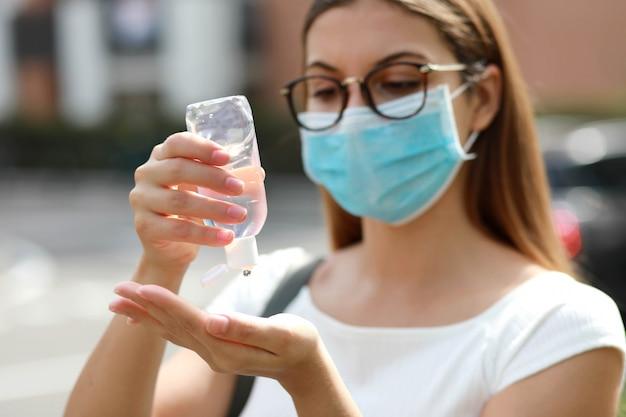 都市通りで手消毒ゲルを使用して医療マスクを持つ少女のクローズアップ。防腐剤、衛生およびヘルスケアの概念。手に焦点を当てます。