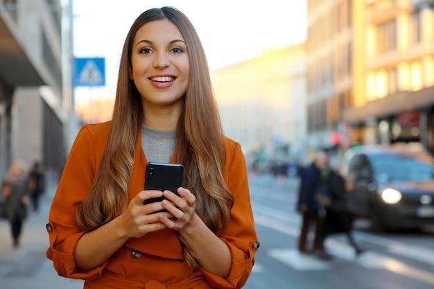 Улыбающаяся женщина с помощью смартфона