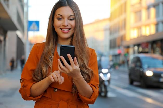 Улыбающаяся женщина, печатающая на смартфоне