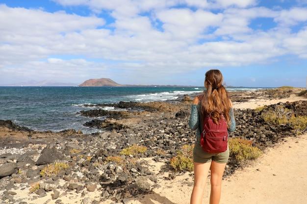 スペインのフェルテベントゥラ島の海に見える若い女性バックパッカーハイキングの背面図