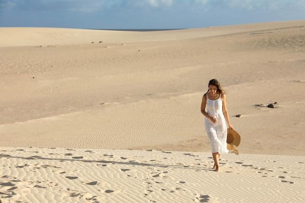 白いドレスと帽子の孤独な砂漠の砂丘の上を歩く若い女性