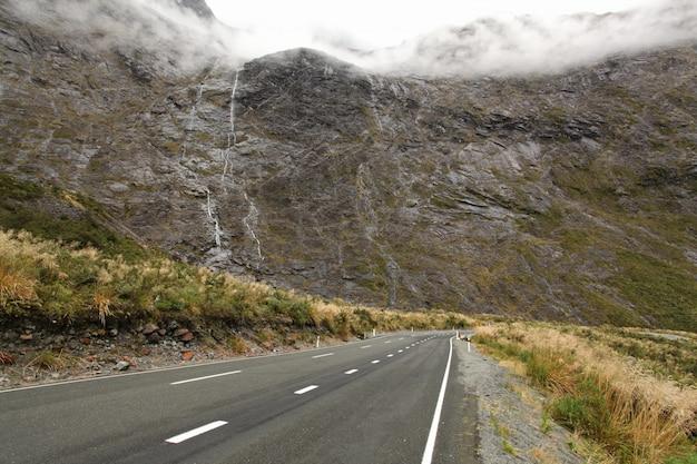 ニュージーランドのフィヨルドランド、ミルフォードサウンド道路沿いの滝のある山