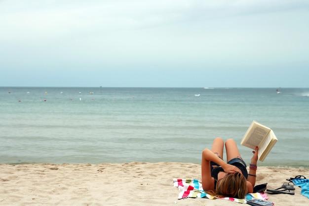 サムイ島タイの熱帯のビーチでリラックスした気分で本を読んでいる女の子