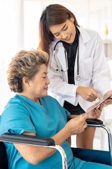 Доктор используя таблетку с старым пациентом