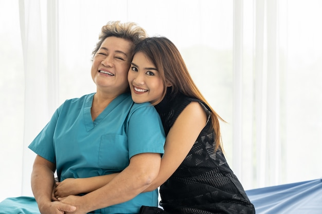 Дочь обнимает пожилую маму