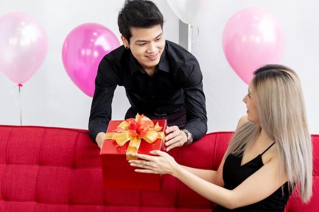 彼の誕生日に彼のガールフレンドに贈り物を与えるボーイフレンド