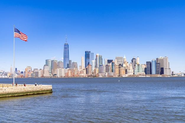 Панорамный манхэттен в нью-йорке и флаг сша
