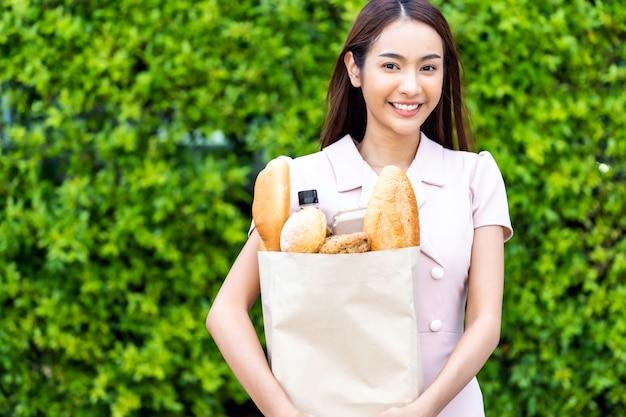 食料品の袋を持つアジアの女性