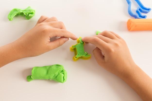 Сенсорная активность. закройте вверх по руке ребенка играя с глиной моделирования теста
