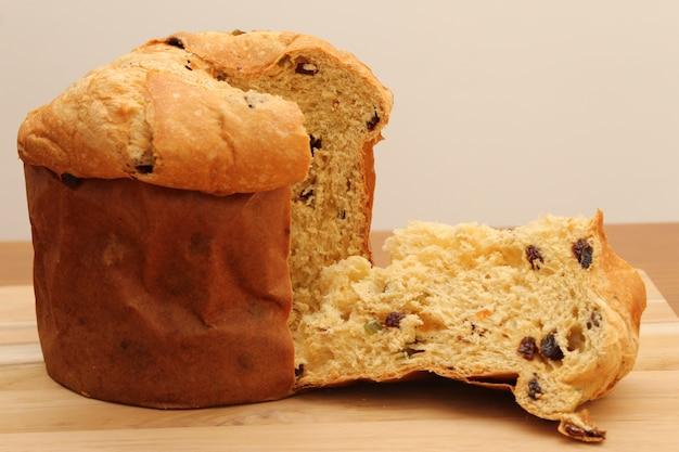 Рождественская еда! вкусный домашний панеттоне (рождественский хлеб или рождественский торт) на деревянной доске
