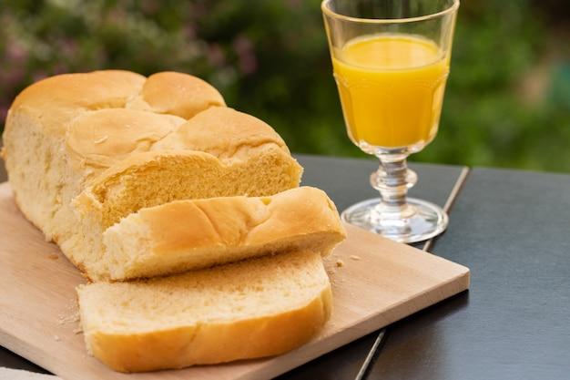 おいしいと柔らかいキャッサバ(ユッカ、キャッサバ、ブラジルマンディオカ)パンとオレンジジュースのガラス。朝食のテーブル。