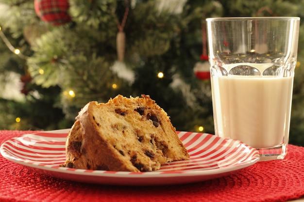 クリスマスの時期:チョコレートの塊とミルクのグラスを添えたパネトーネのおいしいスライス